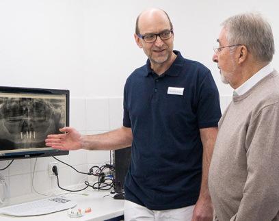 Dr. Moritz zeigt am Bildschirm ein Rötgenbild mit 4 Implantaten